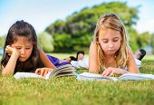Cute Little Girls Reading Books Outside on Grass after School