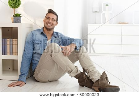 Happy young man daydreaming at home, sitting on floor.