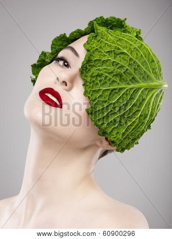 Portrait of a woman illustrating a vegan concept with a cabbage on the head