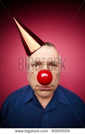 Portrait of unhappy man with a red nose and in a cone cap on fools day