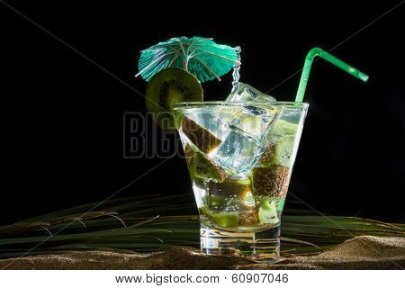 Kiwi cocktail on the sand over black background