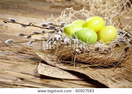 Easter basket with Easter Eggs on wooden background.