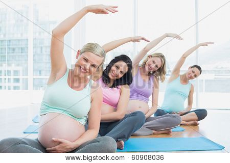 Pregnant women in yoga class sitting on mats stretching arms in a fitness studio