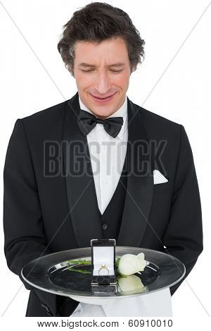 Portrait of smiling server presenting engagement ring and rose isolated over white background