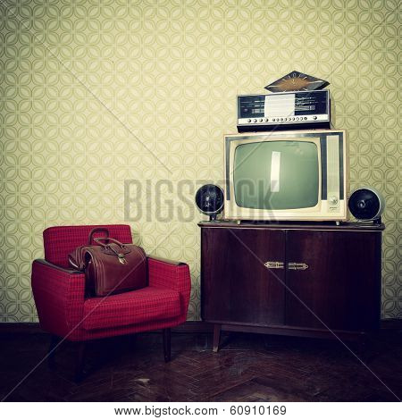Vintage room with wallpaper, old fashioned armchair, retro tv, bag, clocks, radio player and loudspeakers