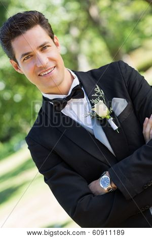 Portrait of confident bridegroom with arms crossed standing in garden