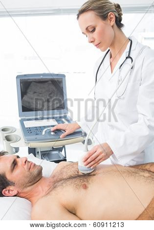 Female cardiologist giving a heart ultrasound to male patient