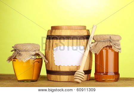 Sweet honey in jars and barrel with drizzler on wooden table on green background