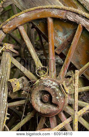 Old Wooden Cartwheel Against Wood Cart