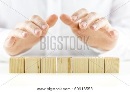 Man Holding Protective Hands Above A Line Of Seven Blank Wooden Cubes