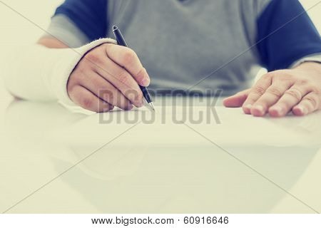 Man With His Arm In A Plaster Cast Writing