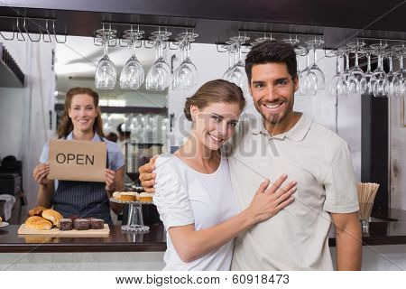 Portrait of a loving couple with female cafe owner at the coffee shop