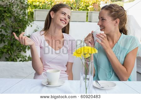 Two happy female friends having coffee at the coffee shop