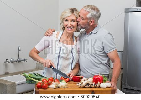 Mature man kissing woman as she chops vegetables in the kitchen at home