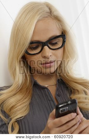 Pretty blonde woman in black framed glasses, using mobilephone.
