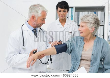 Male doctor measuring blood pressure of a senior patient in the medical office