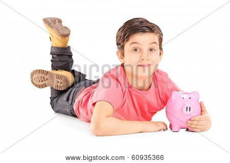 Cheerful boy laying on the floor and holding a piggybank isolated on white background