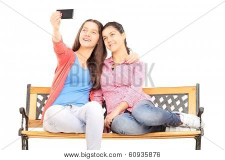 Two young girls seated on bench taking picture of themselves with cell phone isolated on white background