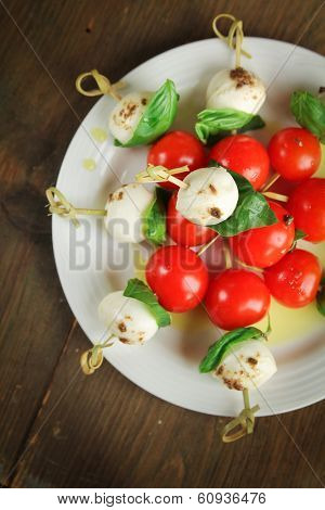 Top view of delicious skewer with bocconcini, cherry tomatoes and basil or caprese