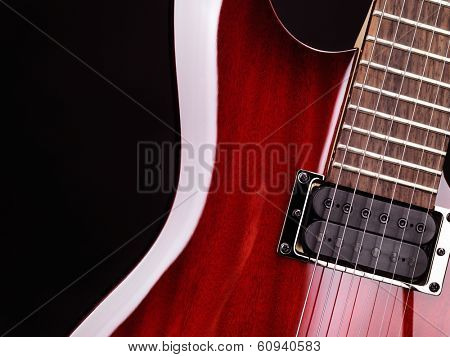 Closeup of red electric guitar neck, strings and pickup