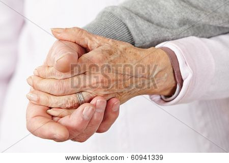 Two happy senior citizens holding their hands close