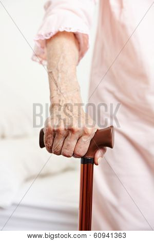 Wrinkly hand of senior woman with walking cane
