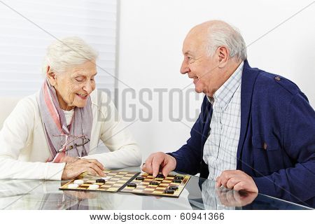 Happy senior couple playing checkers together in a retirement home