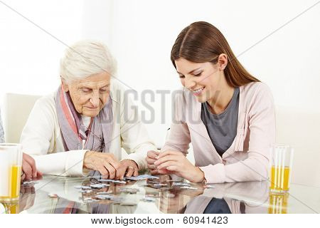 Happy grandchild playing a jigsaw puzzle with her grandmother