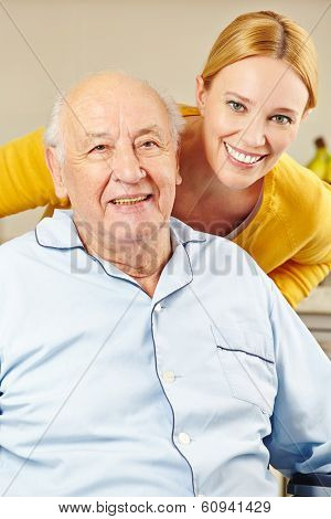 Woman and old man in wheelchair smiling together