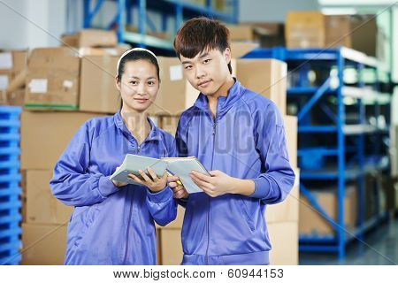 two young chinese workers in uniform at warehousing