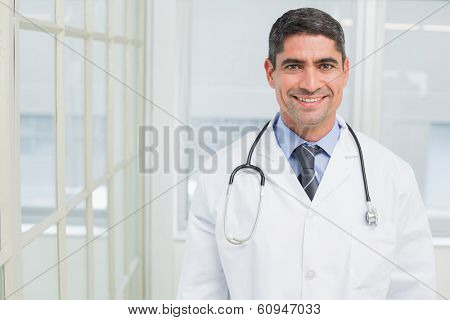 Portrait of a smiling male doctor standing in the hospital