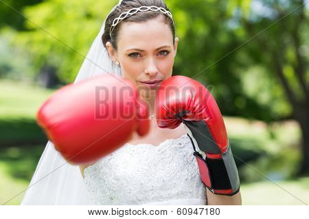 Portrait of confident young bride with boxing gloves punching in park