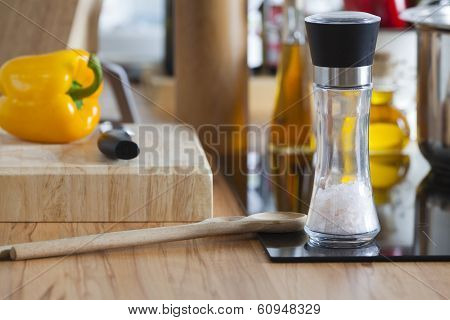 Salt Mill And Cooking Spoons Are On Modern Ceramic Hob