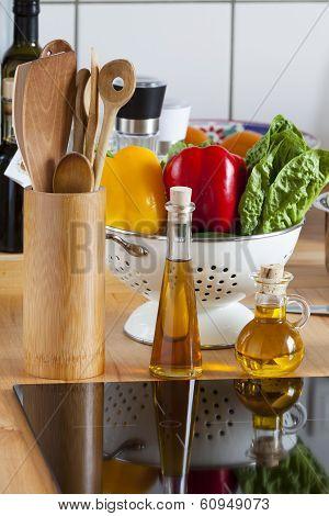 Cooking Spoon Rack, Vegetable, And Olive Oil On Worktop