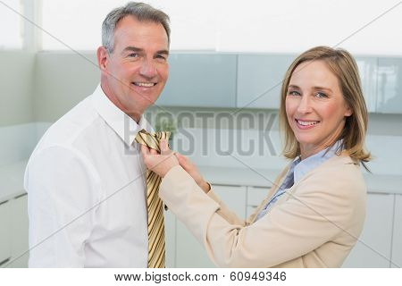 Side view of a woman adjusting businessman's tie in the kitchen at home