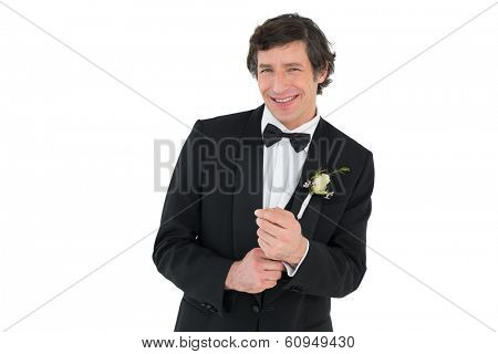 Portrait of happy man adjusting cuff links before wedding over white background
