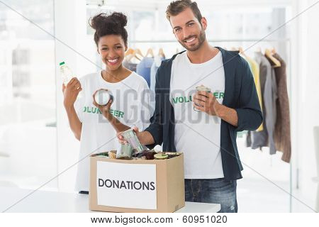 Portrait of a smiling young couple with donation box