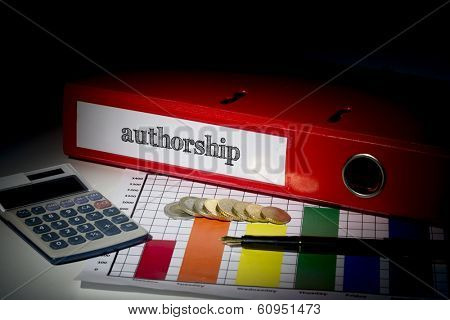The word authorship on red business binder on a desk