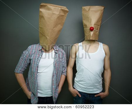 Two guys standing in front of camera in paper bags celebrating fool�¢??s day