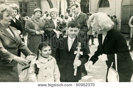 LODZ, POLAND, SEVENTIES - Vintage photo of Vintage photo of little boy with his family at his First Communion