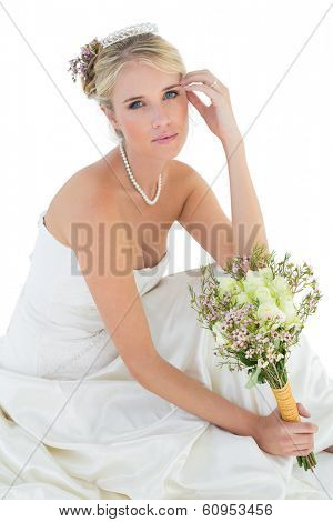 Portrait of sensuous bride holding rose bouquet over white background