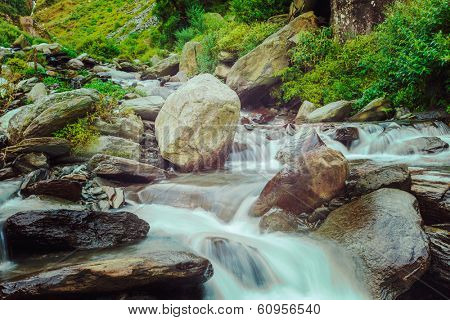 Vintage retro hipster style travel image of cascade of Bhagsu waterfall in Himalayas. Bhagsu, Himachal Pradesh, India. Polarizer filter used