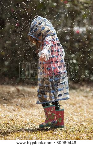 little girl in raincoat and boots walking in rain