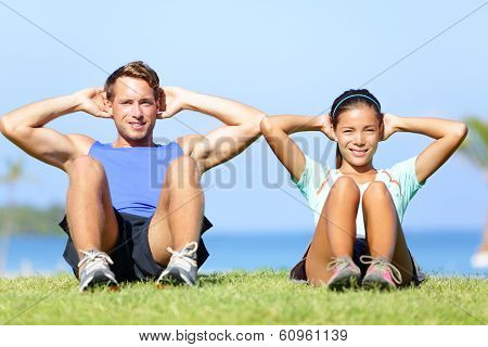 Sit ups - fitness couple exercising sit up outside in grass in summer. Fit happy people working out cross training. Beautiful young multiracial couple, Asian woman, Caucasian man.