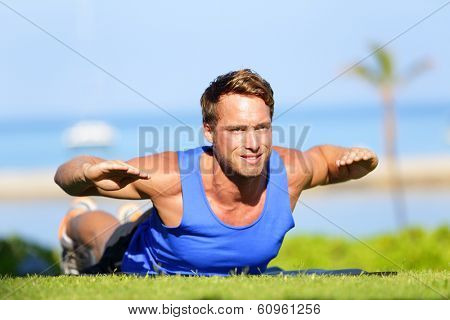 Fitness man training back extension exercise outdoor. Fit male sport athlete exercising lower back during cross training workout outside on grass in summer. Fit handsome muscular sports model.