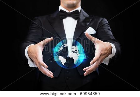 magic, performance and future technology concept - magician in top hat showing globe hologram