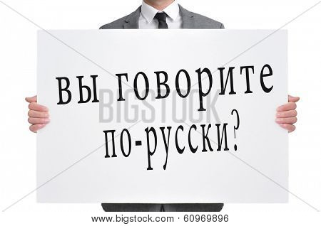 a man wearing a suit holding a signboard with the text do you speak russian? written in russian
