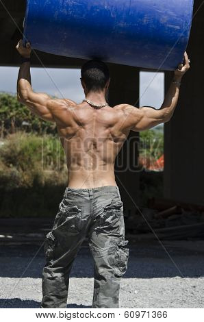Back Of Muscular Construction Worker Shirtless In Building Site Holding Big Barrel