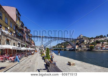 Porto, Portugal - July 27, 2013: Tourists and locals enjoy the Ribeira District scenery and summer sun in the Douro River bank near the Dom Luis I Bridge in Porto, Portugal. Unesco World Heritage.