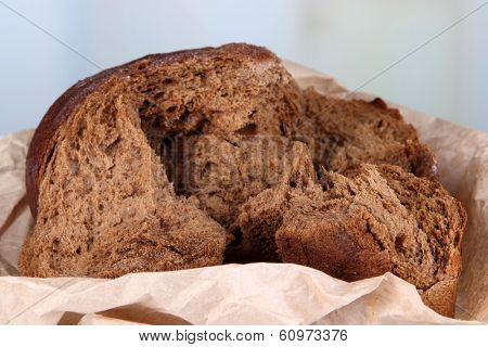 Pieces of bread on paper on bight background